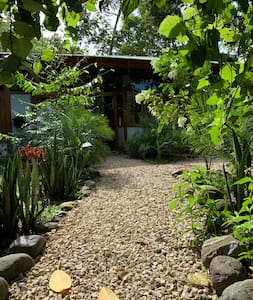 This is the flat path to the home. It is a wide path  bedded with small rocks.