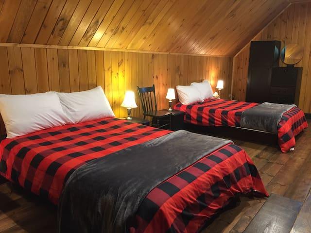 Dans la mezzanine vous trouverez deux lits double. Chaque lit est équipe d'une armoire, deux tables de chevet, deux lampes, une poubelle.  C'est une aire ouverte.