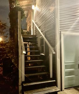 Stairs leading to front door that is well lit with outdoor flood lights and outdoor surveillance cameras.