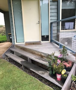 The front door is accessible from the three steps up to the porch from the grass.