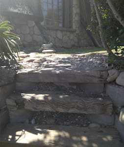 Stairs going up from driveway to cottage.