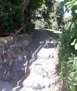 When arriving, go up the driveway and take the path on the right. 3 stone steps with handrail lead up to the front deck.