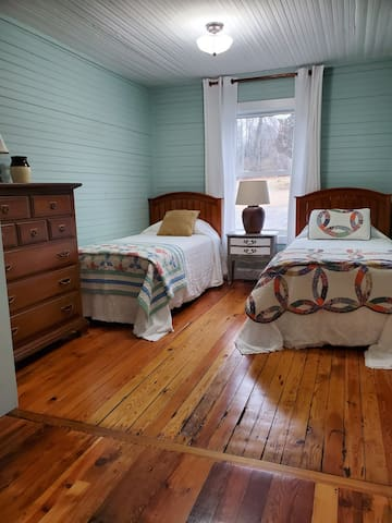 Bedroom with twin beds. Curl up with a quilt for a cozy nap.