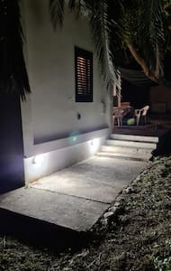 Motion sensor activates lights when you approach the house (before the concrete).