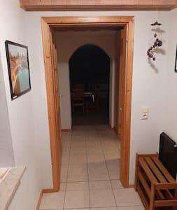 Flur von der Eingangstür bis zur Küche/ Wohnzimmer.  Direkt neben der Wohnungstür ist eine Garderobe und ein Schuhregal.
