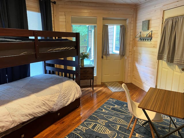 Main floor bedroom with twin bunk beds and a pull out twin trundle. Room has a door connecting it to master bedroom and one to walkout deck.