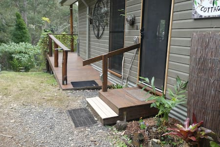 Two entrance options.   1. Front door entrance = two steps with rail or  2. Disability access ramp (suitable for wheelchairs).  Note: We hope to have a concrete pad between both entrances making wheelchair access even easier very soon....