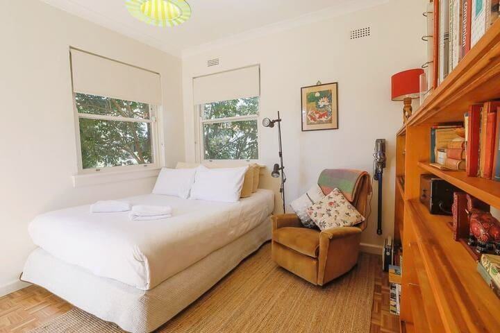 The second bedroom with plush queen bed has a cosy reading nook and direct access to the private balcony.