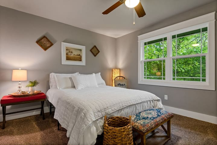 Guest bedroom has a queen bed with cozy linens, a view of the backyard and a small closet.