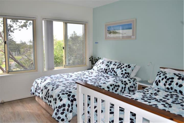 Bedroom 1: This room has a queen and a double bed. There are two large windows and you can hear the waves from the beach at night. This room also has a large built-in wardrobe and features the en-suite and access ton the larger of the two decks.
