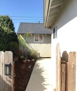 Entrance through the small gate on the left side of the house that has sidewalk lighting.