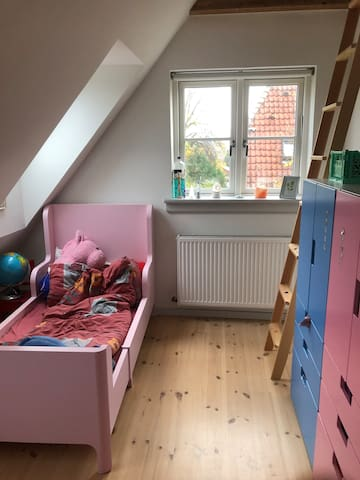 Children room on the 1. floor. with a child's bed, a ladder to a small attic with a matters (and extra bed). 3 windows.