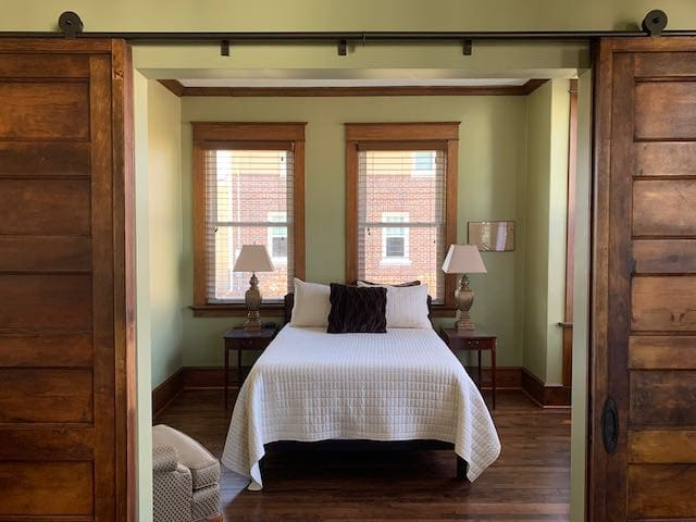 Third bedroom off the living room with antique double bed, side chair, desk and chair