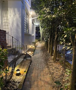 Lighted path surrounds the house, leading guests from the street to apartments and around the property.