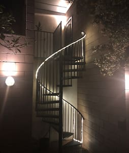 The brick patio from the gate to the spiral staircase is well-lit with dusk til dawn cafe lighting.