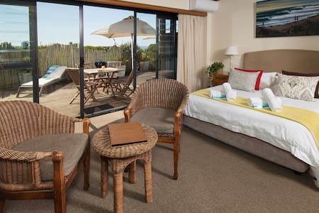 Room 3 - Ground Floor Beach Front Suite in African Perfection 1 on Supertubes, Jeffreys Bay.  Breakfast is included. There is access to a shared kitchenette and a weber is provided for use on your patio.