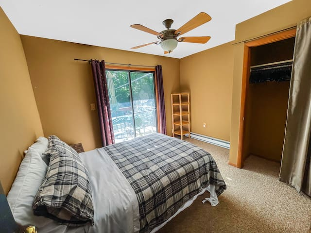 Rear first floor bedroom with full size bed, night stand, closet and sliding patio door to deck and backyard views.