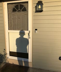 Front door with storm door closed with outside light on a timer.