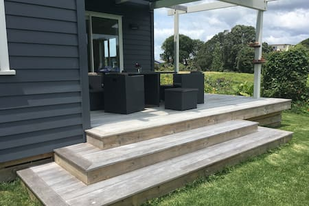 From the driveway there is a clear grass walkway. Leads onto deck with large sliding doors with opening of 1.5x1.5 m wide.