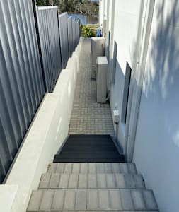 The side path leading down to the guest entrance includes a set of stairs. Motion sensors are installed to turn on lights after dark.