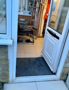 The only rise in this doorway from the flat level pavement to pathway is a 2.5 inch wide step to the double glazed door frame which leads into a level floor porch.