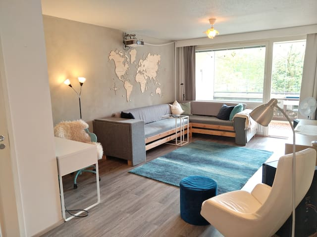 Spacious livingroom with a big sofa, screen and office desk.