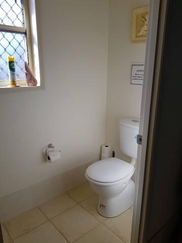 Toilet has a closing door for privacy.