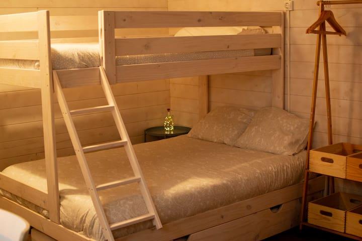 Habitación. Consta de una litera con cuatro plazas (cama doble, cama individual arriba y cama nido individual abajo), mesita de noche y burra con perchas y cajas de almacenaje para ropa.