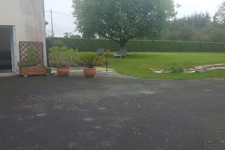 parking goudronné plat situé devant l'entrée du logement