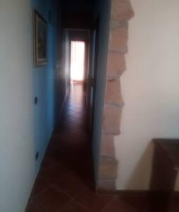 Piccolo corridoio senza nessun gradinono dove c'è la possibilità di percorrere il corridoio senza nessun gradino e da lì si arriva in altre due stanze scendendo a desta e la porta frontale alla foto si ha l'accesso al bagno