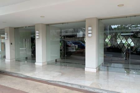 Entrada principal al edificio con una pequeña rampa para sillas de ruedas.