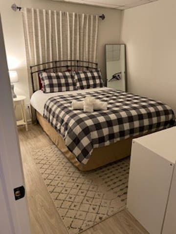 Bedroom 1 complete with a Queen bed, corner clothing rack & full length mirror.