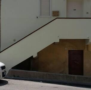 Rampa di scale illuminata che conduce alla porta d'ingresso  (in alto). I gradini sono dotati di strisce antiscivolo.