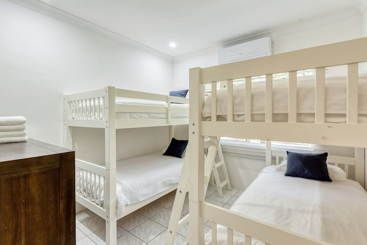 Main house bunk room with four single beds.