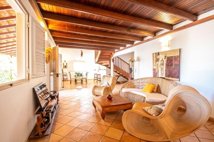 Coin salon meublé d'un canapé et de fauteuils originaux et confortables avec une vue sur la salle à manger sous le beau plafond aux essences tropicales