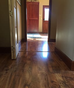 """This is the path from the main door to the suite. Hallway between common area and suite (note bi-fold door that separates suite from rest of the house).  Hallway is 36"""" wide at  bi-fold door. T-molding is ~3/8"""" bump. Bath and main bedroom to right."""