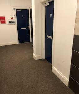 Wide hallway approaching the door to The Nook