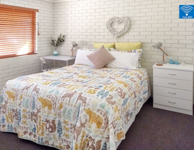 Bed 2: A luxurious queen bed, with lots of storage (wardrobe & chest of drawers), desk & chair.  A ceiling fan and large window (with security screen) provides lots of air circulation.
