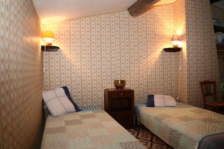 Chambre 4 mansardée en grenier. Deux lits (1890x80). Petite fenêtre sur rue. Accès via chambre 3.