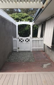 There is also this side gate, which opens towards the ocean. The surface is also flat. To the left, is a side sliding door into the house, and to the right, is the garage, where key pad is kept in lock box. All flat and wide