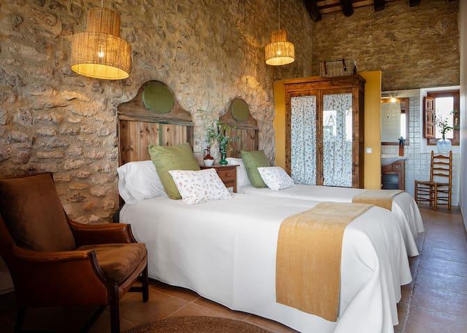 5. Moscatell Situada en la galería. Dispone de dos camas y opción a dos camas adicionales y lavabo con ducha.