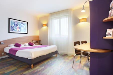 Chambre avec lit double, coin bureau et écran de TV.