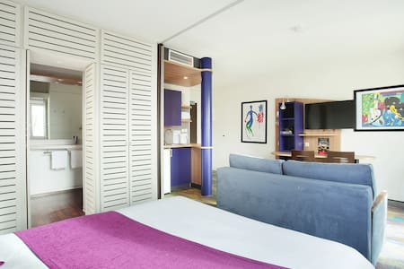 Suite avec lit double, sofa convertible, coin bureau, TV, kitchenette toute équipée, salle de bain.