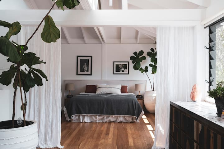The huge bright and airy Master King bedroom that opens out to the upstairs living room.  The north-facing louvres let through the amazing sea breezes.  Listen to the waves while you sleep.