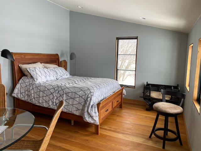 The ELM house EAST room has a queen-size bed, dining glass table with four chairs, a large open wardrobe, a refrigerator, a coffee maker and two other chairs