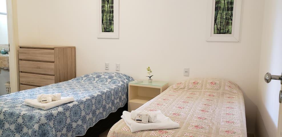 Suite 03 - 1º Andar - vista parcial da cama de casal, estante e sanitário