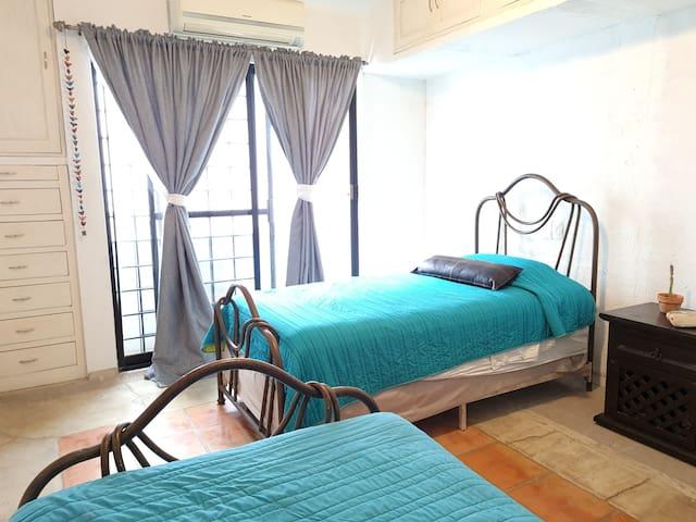 Habitación Doble con excelente iluminación, aire acondicionado y balcón con vista al jardín.