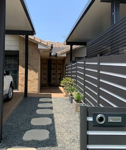 Pathway to the door with solar lights to the side and a light on the corner