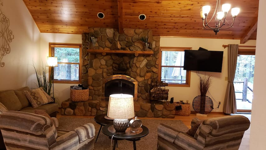 Open concept living room with field stone wood burning fire place (we include wood and kindling) couch opens up to queen size sleeper.