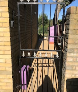 The entrance is via the black iron gate to the right of the house, there is a key safe on the wall to the left of the gate, just walk a long the path to the decking and you will see the oak French doors which lead to the studio.